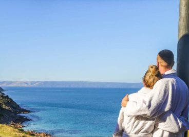 Young couple enjoys weekend getaway in Kangaroo Island. Looks at oceanviews from deck at Sea Dragon Lodge & Villas.